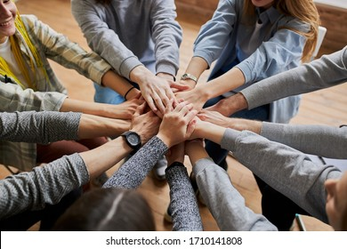 top view on people hands holding together, friendly team work at meeting. club of anonymous alcoholics