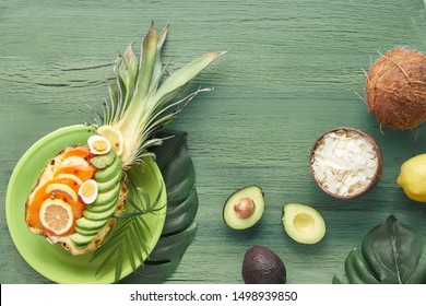 Top view on pinapple boats with smoked salmon and avocado slices with lemon and quail eggs, flat lay on green textured background
