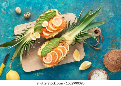 Top view on pinapple boats with  smoked salmon and avocado slices with lemon and quail eggs, flat lay on textured background
