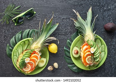 Top view on pineapple boats with smoked salmon and avocado slices with lemon and quail eggs, flat lay on dark textured background