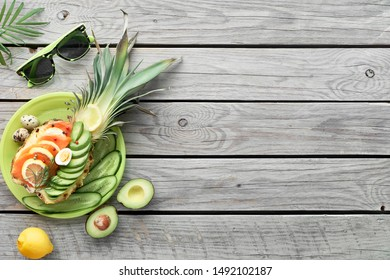 Top view on pineapple boats with smoked salmon and avocado slices with lemon and quail eggs, flat lay on old wooden table