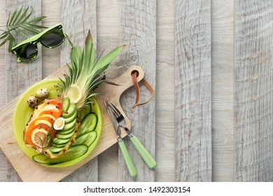 Top view on pineapple boats with smoked salmon and avocado slices with lemon and quail eggs, flat lay on old wooden table, copy-space