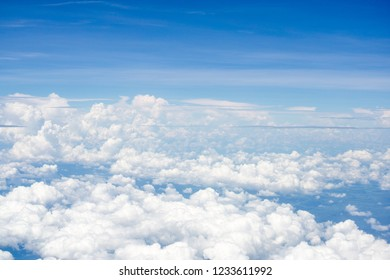 Top view on plane of Blue sky and white puffy clouds.