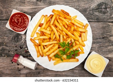 Top view on a plate with french fries and bowls with mayonnaise and tomato sauce