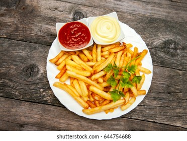 Top view on plate with french fries, tomato sauce and mayonnaise in small bowls on wooden table
