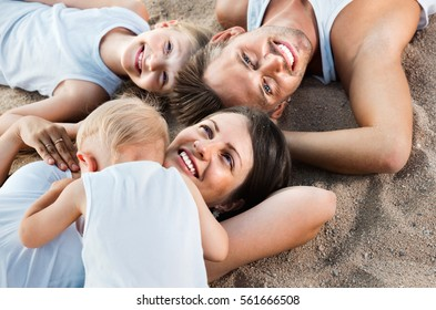 Top view on  positive  parents with kids relaxing on sandy beach on sunny day