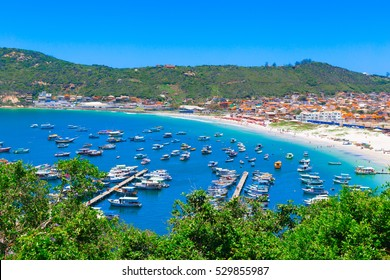 top view on praia dos anjos in arraial do cabo village near rio de janeiro in brazil, many fishing boats in small harbor and public beach with white sand and turquoise water
