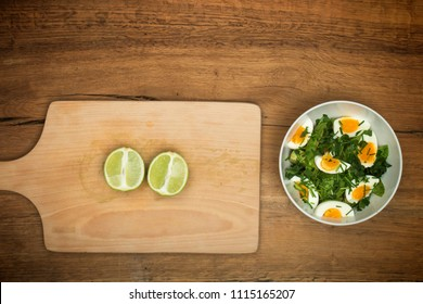 Top view on preparation of avocado with eggs salad recipe on rustic wooden table.