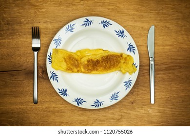 Top view on preparation of omelette served on ornamental plate and rustic wooden oak table.