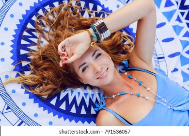 Top view on   pretty redhead smiling woman   lying on beach towel, having fun, spending great time on the beach.Boho accessories .