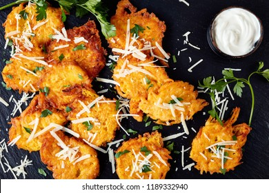 Top view on pumpkin pancakes with grated parmesan cheese, seasoned with chopped parsley served with sour cream sauce on a black stone board, on a black wooden background, close up