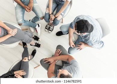 Top view on rebellious teenagers sitting in a circle while talking to a counselor