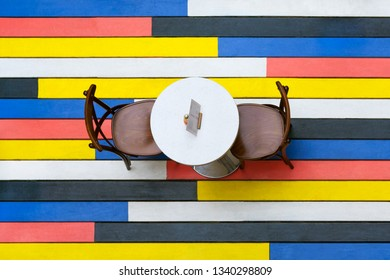 Top view on a round table and chairs on a multi-colored wooden floor in cafe