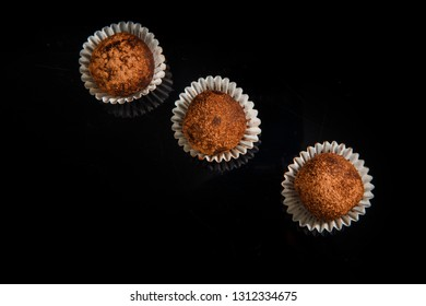 top view on row of three healthy useful organic handmade round chocolate candies decorated with brown cocao powder on black mirror background