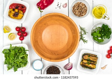 Top view on salad preparation. Wooden bowl with food ingredients around the white rustic table.