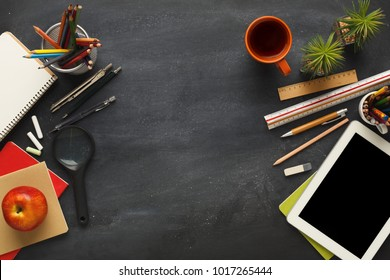 Top view on school educational supplies. Desktop with digital tablet, ruler, pencils, pens, notebooks, magnifying glass and cup of coffee. Studying and researching background, copy space