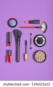 Top view on set of beauty products: decorative cosmetics as lip stick, mascara, eye shadow, blush, balls powder, nail polish and makeup brushes on bright purple background