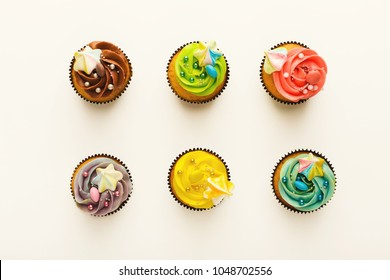 Top view on set of vanilla cupcakes with colorful buttercream tops isolated on white background. Tasty desserts in brown muffin liners. Delicious treats for birthday party, bakery concept, cutout