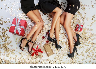 Top  view on  sexy women legs   on  background of shining golden  confetti,  gift boxes, glasses of champagne. Celebrating time.