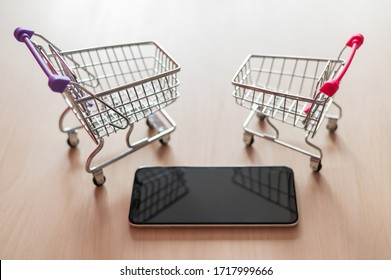 Top view on a shopping cart and mobile phone on a wooden table. Smartphone online shopping. Online shopping.