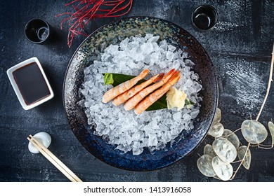 Top view on shrimp sashimi served on bowl of ice on dark background. japanese food sashimi. Japan restaurant menu. Copy space for design. Top view seafood. Healthy meal