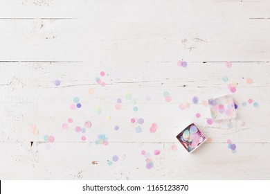 Top view on small box full of colorful confetti on white wooden table. Holiday season. Celebration.
