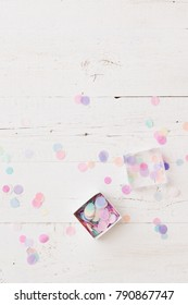 Top view on small box full of colorful tissue paper confetti on white wooden table background.