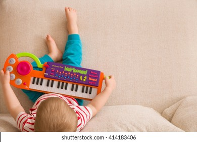 Top view on small cute toddler boy sitting on the sofa and playing on the toy piano. A little boy learning to play piano listening to music. Early development for toddler. Musical education for kids