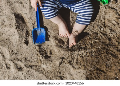 top view on small kid legs playing in sand. background for summer vacation with children. cute baby toes in the sand.