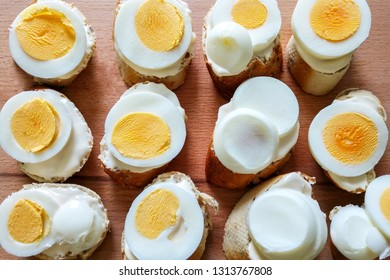 Top view on small sandwiches of white bread, cheese and chopped eggs with yolk, lying on a wooden board