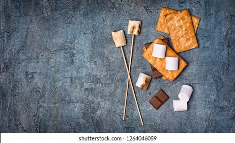 Top view on sticks with roasted on campfire marshmallow, crackers and chocolate as ingredients for s'mores on blue concrete background with copy space