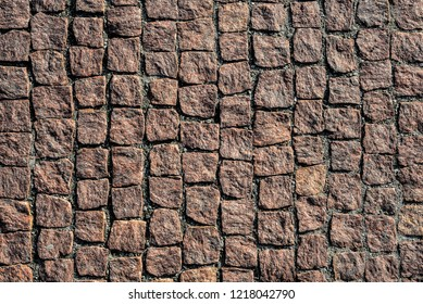 Top view on stone road close up. Old pavement of granite. Brown square cobblestone sidewalk. Mock up or vintage grunge texture.