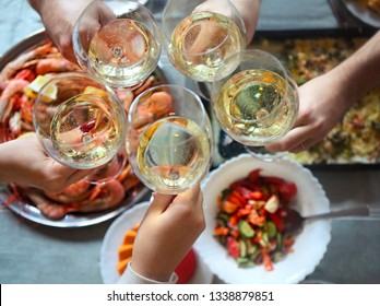 The top view on a table with food and toast with white wine. Gratin, salad and seafood on the table