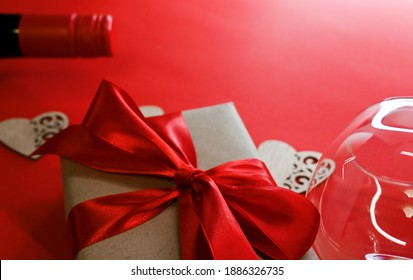 Top view on a table for Valentines day with bottle of wine champagne, two glasses, gift box with red ribbon bow, heart shaped candies and envelope on red background.