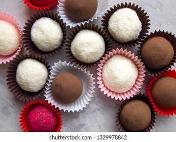 Top view on tasty chocolate truffles. Different variants of candy: white coconut truffles, cocoa truffles and pink raspberry bonbon.