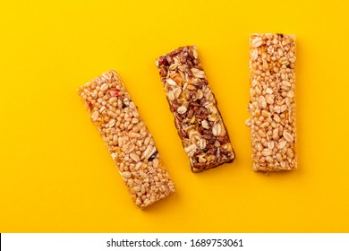 Top view on three granola bars on yellow background. Puffed rice, berries, chocolate and oatmeals.