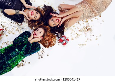 Top view on three surprised woman lying on the floor, celebrating new year or birthday party. Wearing luxury sequins dress and jewelry. Golden shining confetti , red gift boxes. Space  for text.