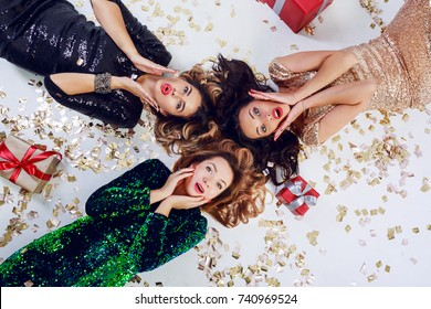 Top view on three surprised woman  lying on the floor, celebrating new year or birthday party. Wearing luxury sequins dress  and jewelry. Golden shining confetti , red gift boxes.