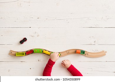 Top view on toddler's hands with toy wooden train on railway. Child's hands playing with educational toys.