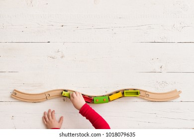 Top view on toy wooden train on railway. Child's hands playing with educational toys.