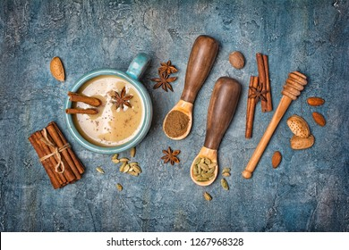 Top view on traditional indian drink masala chai tea with milk and spices as cinnamon stick, green cardamom, anise star and nutmeg on blue concrete background