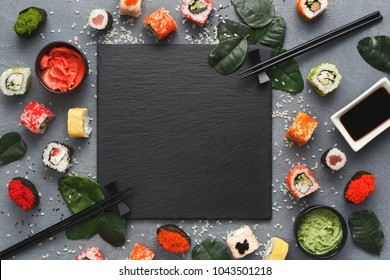 Top view on traditional japanese empty square black slate framed with sushi, ginger, soy sauce, wasabi bowls, green leaves and chopsticks on rustic grey background, copy space