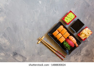 Top view on traditional japanese empty with sushi, ginger, soy sauce, wasabi bowl and chopsticks on concrete grey background, copy space, mockup, flat lay. Online asian food delivery concept