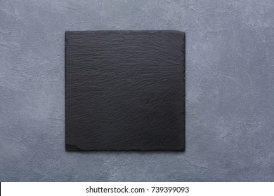 Top view on traditional japanese square black slate plate on rustic grey backround copy space