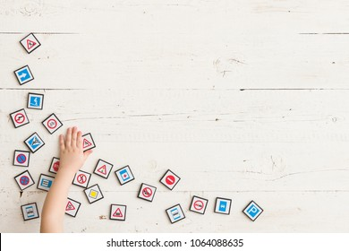 Top view on trafic signs game with boy's hand on white wooden table background.