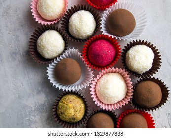 Top view on truffle sweets in wrappers. Different types of candy: dark chocolate truffle in cocoa, white coconut truffle, red candy covered with sublimated raspberries, candy covered in nut crumbs.