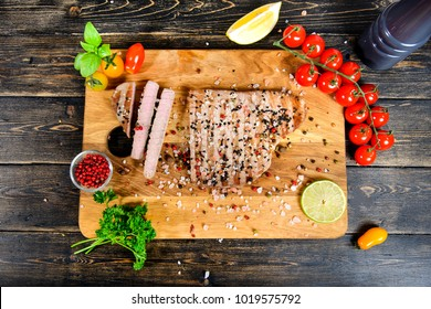 Top view on a tuna steak lying on a cutting board with herbs and spices. The cutting board stand on a wooden background.
