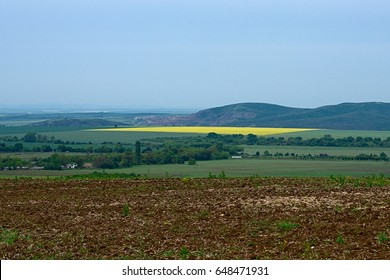 The top view on a valley among the Balkan mountains in spring, the beautiful view of plowed field on the background of village, yellow rapeseed fields and mountains.