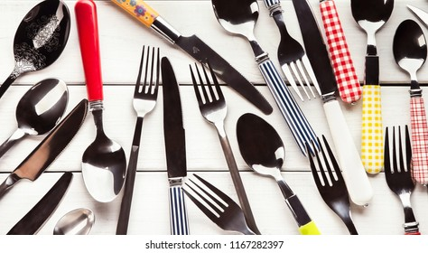Top view on various forks, knives and spoons. Set of assorted cutlery with fancy handles, flat lay on white rustic wooden planks. Antique and modern kitchenwear background