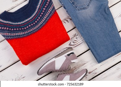 Top view on warm clothes. Bright woolen sweater, regular jeans and sneakers. Fall casual collection.